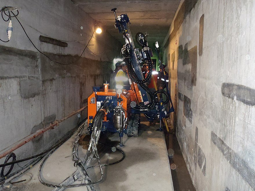 A narrow corridor inside the dam where a small drillrig is drilling with Wassara's water powered hammer