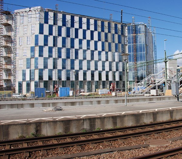 A big conference centre with glass front seen from the train tracks in Lund, Sweden