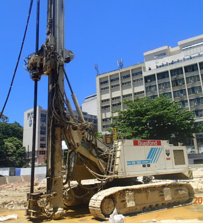 An open worksite with high buildings in the background. On the work site you can see a white drillrig ready to drill with Wassaras water powered hammer