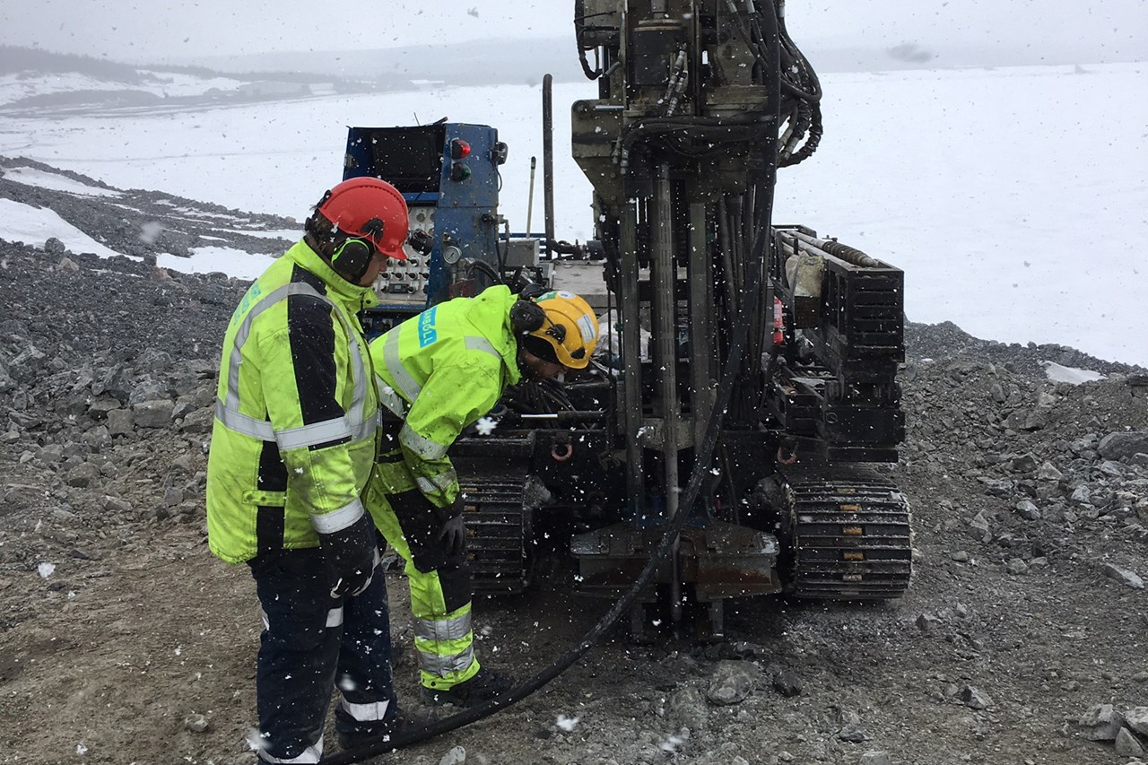 Two drillers in yellow working clothes standing next to a rig at a snowy drilling site