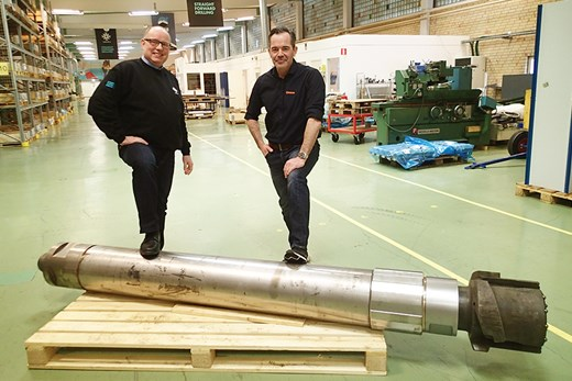 Two men standing behind a large drill hammer - 2,5 meter long